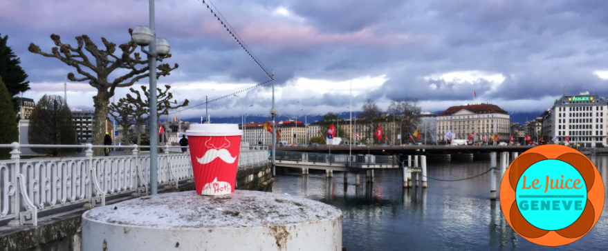 A Boreal paper coffee cup next to lake geneva