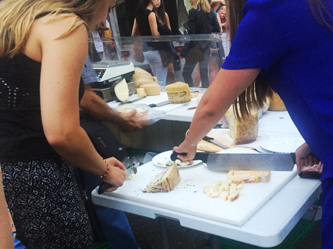 Marchée des Grottes . Two women slice cheese for a platter